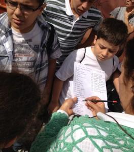 Como os pais tiveram que autorizar o passeio, os professores checam os nomes dos alunos na lista antes do embarque